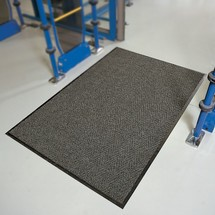 Dust control mat with herringbone pattern